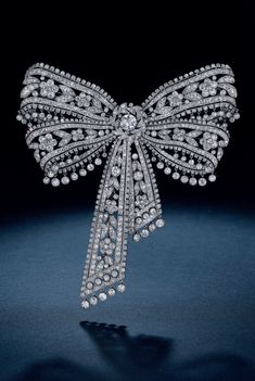 CARTIER - A FINE BELLE EPOQUE DIAMOND BOW BROOCH, CIRCA 1904. An articulated openwork double-bow with old-cut diamond fowers, with a collet-set diamond trim and fringe, centring upon an old-cut diamond knot, within a diamond-set leaf surround, suspending a detachable articulated staggered ribbon of similar design, mounted in platinum, unsigned.