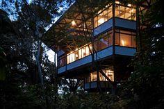 Ao cair da tarde, a silhueta da casa Tijucopava, projetada pelo arquiteto Marcos Acayaba, tem seus contornos emoldurados pela densa vegetação local. Destaques para o balanço da cobertura e dos peitoris brancos em madeira compensada