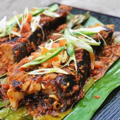 Sambal Grilled Stingray or Skate on Banana Leaf with Spicy Chili Barbeque Sauce, Lemongrass,  Garlic & Cherry Tomato.