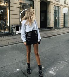 Mini patent skirt paired with grey sweatshirt and black boots
