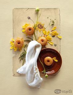 쫄깃한 식감과 건강하고 담백한 맛이 일품인 우리 떡이 봄날을 맞아 색 다 른 멋을 품었다. 형형색색 화사하면서 서정적 감각으로 빚어 담아 한 편 의 도감圖鑑처럼 엮은 꽃 속의 떡을 감상하시길.