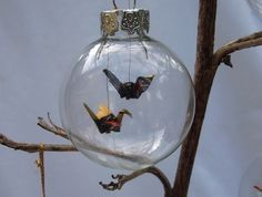 Origami cranes in three glass baubles