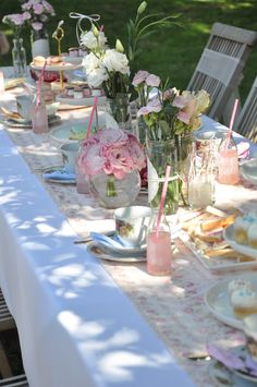 Vintage spring tea. Vintage tea cups, fabric runner, clusters of mason jar vases wrapped with doily and ribbon or raffia and large round vases hold roses and daisies. The color palet is shades of pink and white.