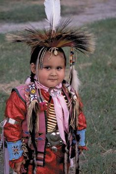 A young Comanche boy is pictured wearing traditional clothing at a Native American celebration in Medicine Park, Oklahoma.