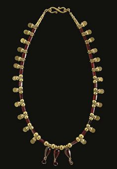 A GREEK GOLD AND GARNET BEAD NECKLACE   HELLENISTIC PERIOD, CIRCA 2ND-1ST CENTURY B.C.   Composed of cylindrical faceted garnet beads, interspersed with gold beads each composed of three large spheres with clusters of granulation in between, a disk flange at the ends, centered by three drop-shaped cabochon garnets in box settings, each with a ribbed suspension loop, rings below joined to uncut garnets, spherical beads in between, tapered collars at the ends; strung with a modern S-hook…