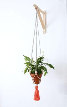 Suspension pour plante en traphilo, avec perle en bois et pompon ne laine.  Nouveau modèle.Couleur gris et corail.