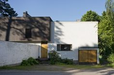 A facade composition in contrasting colours black and white, in size and placement, large and small, heavy and light, brick and wood. One of Alvar Aalto's homes facades, the Aalto house, located in Munkkiniemi area in Helsinki.