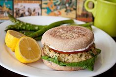 LEMON BAKED TUNA BURGERS: 2, 6 oz cans tuna fish, drained and flaked    1/2 cup panko bread crumbs   1/4 cup finely chopped green onions    3 tablespoons minced fresh parsley    2 cloves garlic, minced     1/4 teaspoon each, salt and pepper     juice of half a lemon   3 tablespoons sour cream  1 egg   4 English muffins   4 leaves romaine    1 small tomato, sliced