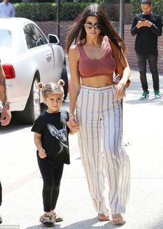 Top of the crops: Kourtney Kardashian, 38, flaunted her cleavage and toned abs in a sassy rose gold crop top as she took daughter Penelope for lunch in Studio City, California, on Thursday