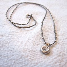 Daintiest crocheted beaded necklace in pearl and gray with silver plated sun stamped charm pendant. $35.00, via Etsy.