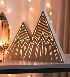 This handmade mountain range night light will add a touch of originality and whimsy to your decor. The light softly glowing from the laser cut pattern on its face, and cast from the open back can either gently light your way in the dark, or add a warm ambiance to any room.  --------------------  S P E C I F I C A T I O N S :  10 tall x 12 wide x 3 deep 25.4 cm tall x 30.5 cm wide x 7.6 cm deep  High quality Baltic Birch plywood Natural bare finish Intended for indoor use  Light fixture: 55…