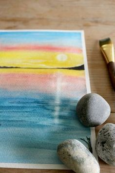 Watercolor sunset painting, using wash and 'lifting' techniques to create the sun and its reflection.