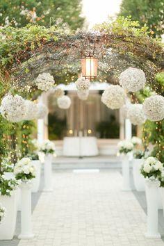 une allée de mariage avec arche en fer forgé, arche mariage décorée de boules de fleurs blancs