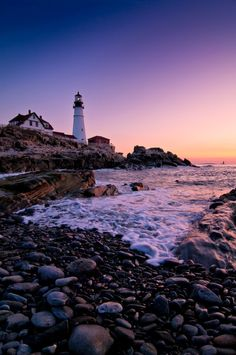 A purple, yellow and orange sunset provides a breathtaking backdrop for one of Maine's most well-recognized lighthouses--Portland Head Light.