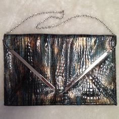 JLO  Jennifer Lopez Envelope Clutch Purse This purse is a larger clutch type purse.  It's in like new condition.  It has a snakeskin pattern with silver trim and a silver chained strap.  The colors are turquoise and brown with a golden shimmer blended through. Jennifer Lopez Bags Clutches & Wristlets
