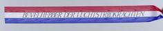Anonymous | Lint 'Bevelhebber der luchtstrijdkrachten', Anonymous, 2000 | Lint met drie horizontale banen rood, wit en blauw, gelegd op 4 mei 2000 bij het Nationaal Monument op de Dam. In de witte baan een opschrift in zwart. Uiteinden recht afgeknipt met kartelschaar. Aan een zijde gebonden met ijzerdraad, dez is gebogen t.b.v. bevestiging aan krans.