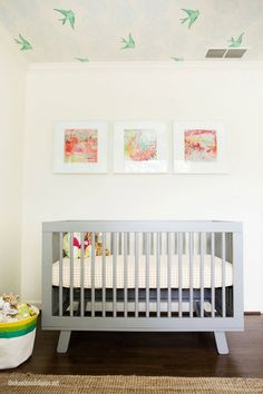 """""""Gender neutral, modern nursery featured on The Handmade Home via Pinterest. White walls, clean-lined crib (very affordable!) and whimsical wallpapered ceiling give the room it's modern feel. Traditional element, such as the tufted glider chair (from Target!), woven rug and changing table balance the look."""