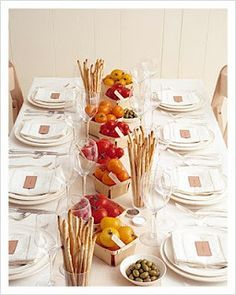 Crisp and clean white table setting with a pop of color from bowls of colorful vegetables. Slim bread sticks complete the look. Tuscan, Italian themed wedding table setting.