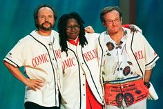 """Robin Williams (R), Billy Crystal (L) and Whoopi Goldberg share a hug on the stage of New York's Radio City Music Hall at the end of HBO's """"Comic Relief 8"""" show, in this file picture taken June 14, 1998. REUTERS/Jeff Christensen/Files"""