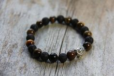 Protected Wanderer bracelet by Wanderbird. Made with lava, tiger's eve and buddha charm. Tigers Eye Gemstone, Lava, Buddha, Beaded Bracelets, Charmed, Gemstones, Trending Outfits, Unique Jewelry, Handmade Gifts