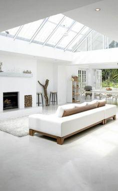 salon avec plafond en verre et canapé blanc et sol en béton ciré gris