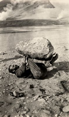 A man balances a piece of pumice rock on his legs in Katmai National Park and Preserve, Alaska, September 1921.Photograph by Lucius G. Folsom