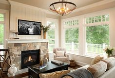 Family room. Isn't this room perfect to relax with a cup of coffee or to watch your favorite show? I love the shiplap above the fireplace mantel. Wall paint color is Benjamin Moore OC-15 Baby Fawn, the stone fireplace is a custom blend and ceiling features grasscloth wallpaper. Ceiling light is Murray Feiss. #familyroom Vivid Interior Design. Hendel Homes