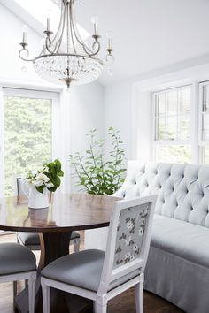 French Hollywood Regency Traditional Entertaining: A feminine breakfast nook with a tufted banquette, crystal chandelier, and round, wood pedestal table.