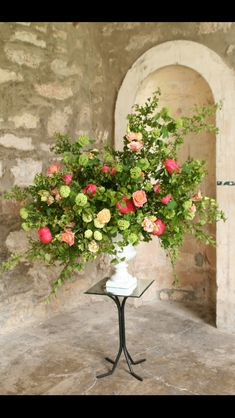Urn arrangement with mixed seasonal foliage and pops of coral flowers.