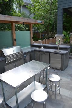 This backyard sanctuary was designed to be a peaceful retreat as well as the perfect spot for entertaining. A small cedar pergola provides shade, while tempered glass panels offer privacy. A grill, small outdoor refrigerator, and sink and concrete countertops make meal prep a breeze.