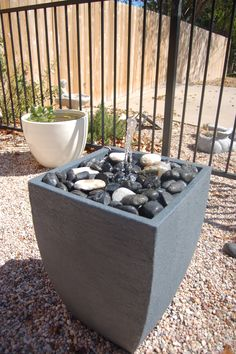 DIY Water Feature - convert planter to a bubbling water feature. water feature, pea gravel and iron fence. love