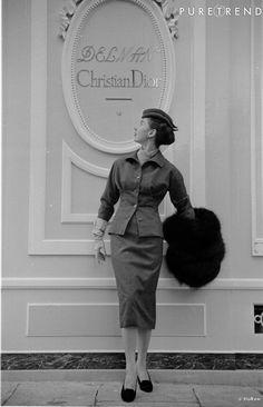 Août 1953, mannequin portant un tailleur jupe, et posant devant une boutique Christian Dior.