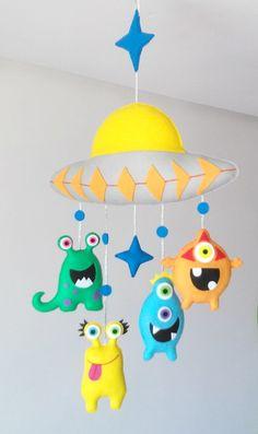 Móbile feito de feltro, costurado a mão e preenchido com fibra siliconada.    São quatro monstrinhos de aproximadamente 12 cm de altura, presos em um disco voador. Sua leveza, o seu colorido e mobilidade traz calma, distração e alegria para o seu bebê.    Deixa qualquer ambiente alegre e divertid... Kids Crafts, Baby Crafts, Felt Crafts, Diy And Crafts, Arts And Crafts, Baby Room Decor, Nursery Decor, Hanging Crib, Felt Animal Patterns