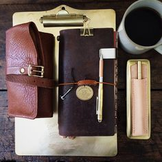 | today's tools • leather + brass • and always with coffee | #liveauthentic #livefolk #coffee #onthetable #nothingisordinary #viewfromabove #coffeetime #midoritravelersnotebook #midori #travelersnotebook #travelersnote #travelersfactory #planner #journal #stationerylove #stationery #leathercraft #ateleiacraft #thesuperiorlabor #workspace #baumkuchenstudio #vsco #vscocam