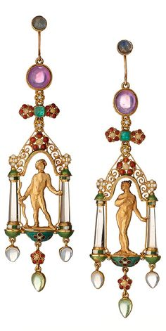 A pair of Victorian enamel and gem-set Earrings, Henry Wilson, London, circa 1900. With cast and chased figures of Psyche and Cupid standing beneath a baldachin of enamel and scrolling gold filigree, carved rock crystal columns with striped enamel terminals, suspending pear shaped drops of moonstone and peridot, all hanging from cabochon moonstones and pink star sapphires with a row of flower heads centred by sugarloaf emeralds. 8.2cm.