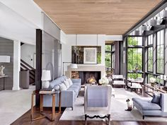 An artwork by Terry Winters overlooks the Nashville, Tennessee, living room of interior designer Ray Booth and television executive John Shea. Roust, one of their two Siamese cats, strikes a noble pose next to a Minotti chaise longue. A Christophe Delcourt floor lamp and a Robert Lighton side table flank the sofa, also by Minotti; the carpet is by Stephanie Odegard Collection.