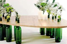 wine tasting tables.....wooden table tops with holes cut out for the table's wine bottle legs.....the Dvinus sets also include ingenious elevation systems using wine corks, candle holders and snack bowls created using bottle necks.....   by Dvinus Collection creator and Spanish designer Tati Guimaraes.... :-)