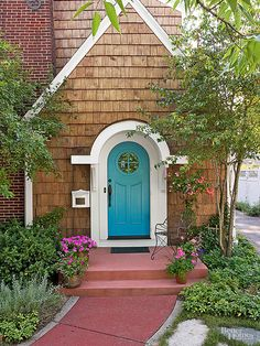 Substantial white casing highlights a turquoise door that makes a splash thanks to its complementary color partners. When choosing a blue hue for your front door, consider the color of walkways and exterior siding (here, it's brick red and rusty tan). Select a shade found on the opposite side of the color wheel to fashion noteworthy contrast.