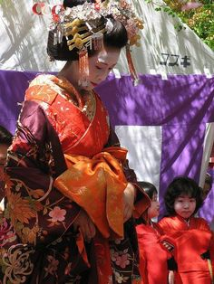 A woman dressed as a tayuu along with two kamuro.
