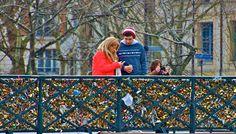 Love locks on the Pont de l'Archevêché and a couple embracing in Paris, France