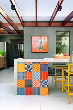 Bancada de concreto e pergolado de madeira e policarbonato em varanda de 54 m², com projeto do arquiteto Bruno Reis e da designer Helena Kallas, do escritório Mandril Arquitetura.