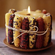 Alternate light and dark colored ears of Indian corn around a fat cream colored pillar candle and tie the whole thing with some rustic string.