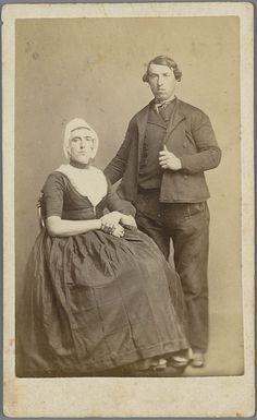 Man en vrouw in Walcherse streekdracht. Beide zijn gekleed in zondagse dracht of uitgaansdracht. De vrouw draagt onder de 'trekmuts' een ondermuts, waarin het oorijzer is gespeld. Aan de uiteinden van het oorijzer bevinden zich gouden windingen, de 'krullen'. Aan de krullen hangen klaverbladvormige oorijzerhangers. In de uitsnijding van het jak is de beuk (kroplap) zichtbaar. Op de schoenen worden schoengespen gedragen. 1875-1890 #Zeeland #Walcheren