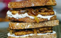Tempeh is sandwiched between two slices of sourdough bread, then topped with a cashew cheese, and caramelized apples and onions.