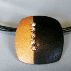 black and gold polymer clay pendant with gold swarvoski crystals