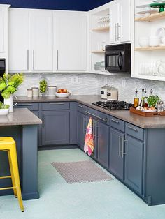 It took just $700 to transform this once drab kitchen. The cabinets were given a fresh coat of paint and new hardware, while the floor received a facelift in the form of a stenciled pattern. A new gray-and-white tile backspla