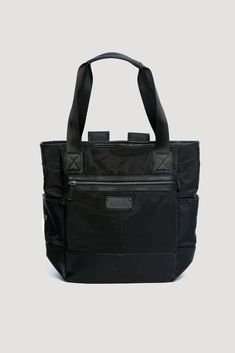 This Lolë tote bag is the brand& top seller across all categories. It can convert into a backpack, has a pocket for a yoga mat and several multifunctional pockets, as well as secured zippers. It& a must-have for the woman with an active lifestyle! Nylons, Packable Jacket, Lol, Gingham Shirt, Beach Tops, Leggings, Bucket Bag, Diaper Bag, Gym Bag