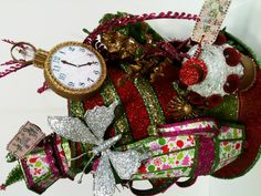 """Alice in Wonderland Mad Hatter Hat Christmas Tree Topper made completely from paper, cardboard, foamboard, and wire. Mad Hatter's Hat elements include: Teapot, """"Drink Me"""" teacup, """"Eat Me"""" Red Queen crown cupcake, White Rabbit's pocket watch, """"This Way, That Way"""" sign posts, and Christmas presents. Also includes floral elements. All pieces were designed and handmade by me with the exception of the glass mushroom and the floral stems. One of a kind commissioned piece."""