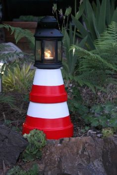 DIY - Clay Pot Lighthouse - Supplies: candle lantern or solar light clay pots (various sizes that stack) primer spray paint outdoor craft paint ruler pencil paint brush and glue (or similar) Clay Pot Projects, Clay Pot Crafts, Diy Clay, Diy Crafts, Pots D'argile, Clay Pots, Garden Crafts, Garden Projects, Clay Pot Lighthouse
