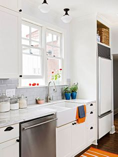 So similar to my future kitchen! Grey and white overall scheme with oil rubbed bronze pulls and light fixtures. Well used built in space over the refrigerator too! - via BHG